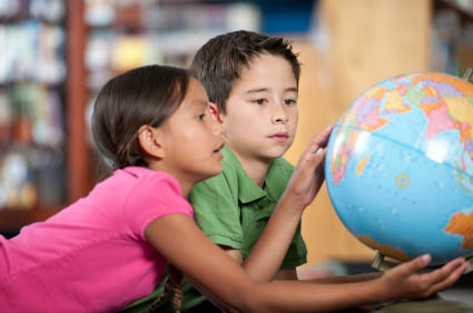 elementary students looking at a globe